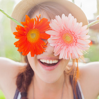 young-woman-holding-flowers-over-her-eyes_web